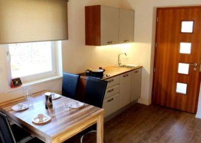 Melanies Guesthouse Kaltern Blick auf Esstisch und Küchenzeile